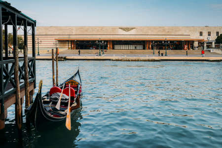 Venetian gondola on the Canal Grande with Saint Lucia railway station, the main railway hub in Venice, in the background