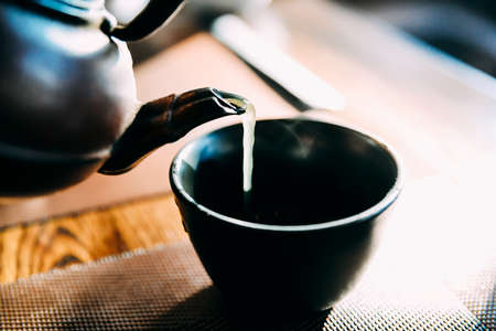 Close up pouring a hot Japanese green tea kettle on an oriental style cup on table - natural light