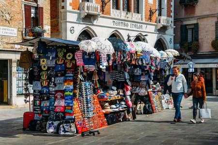 Pedestrians walk beside market stalls set up in the Cannaregio district of Venice