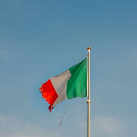 Italian flag on the mast blowing in the wind with ripped corners, perhaps a metaphor for a series of political and economic crisis facing the country
