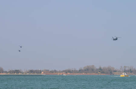 Military Helicopters in formation over the Venetian lagoon heading towards Aviano Air Base in Northeastern Italy