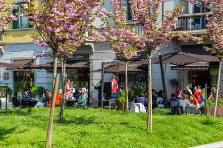 Locals relax and drink coffee at a restaurant patio on a sunny morning Foto de archivo - 111153357