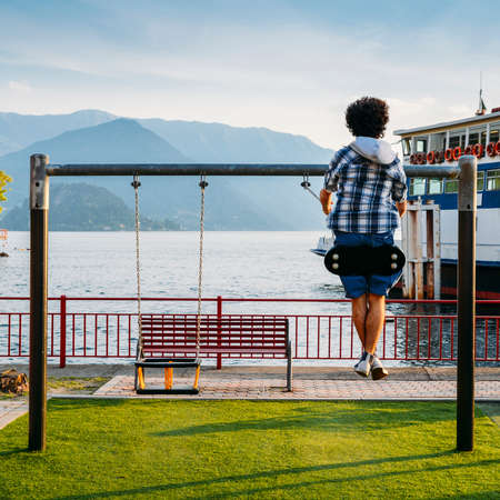 Unidentifiable teenager plays on a swing overlooking Lake Como, Lombardy, Italy