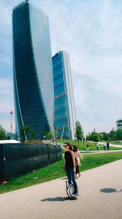 A young woman is captured an electric unicycle at Milans CityLife district park, a modern business park in the city