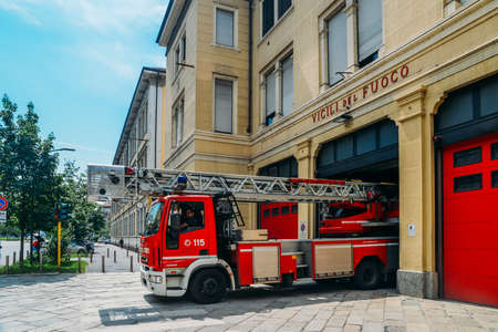 View of a red fire truck parked just outside a fire station in the city of Milan, Italy Banque d'images - 111153492