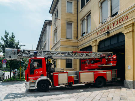 View of a red fire truck parked just outside a fire station in the city of Milan, Italy