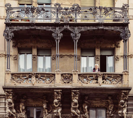 Older woman on balcony of typical residential palace at the Porta Venezia neighbourhood. The architecture is early 20th century nature inspired Liberty, art-noveau style Archivio Fotografico - 111153656