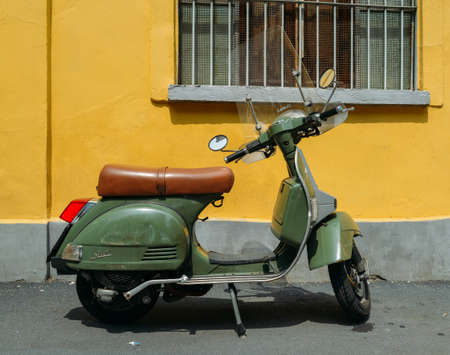 Green Piaggio Vespa LML T5 150 parked on side of street with yellow background Editorial