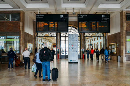 Passengers look at the digital timetable display inside Lisbons Santa Apolonia train station connecting Portugals inter-city train network is accessible Editorial