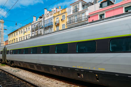 Portuguese train on platform at Lisbons Santa Apolonia train station. Background of typically Portuguese colourful buildings Editorial