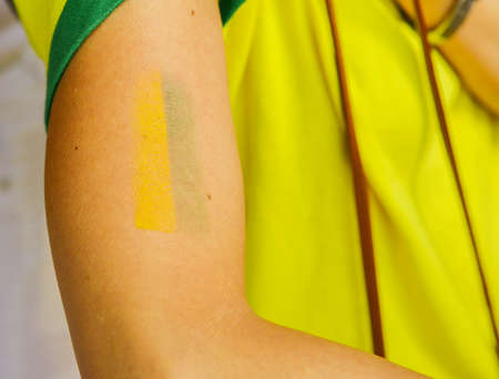 Tattoo an arm with yellow and green symbolizing the Brazilian football or soccer team, with iconic yellow jersey, supporter of world cup concept.