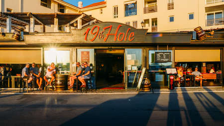 British tourists and expats relax with some drinks and conversation at the terrace of a pub entitled 19th hole. Algarve is a popular golfing destination