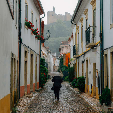 Narrow cobblestone street looking towards the 12th-century Convent of Tomar -Tomar, Portugal Stock Photo
