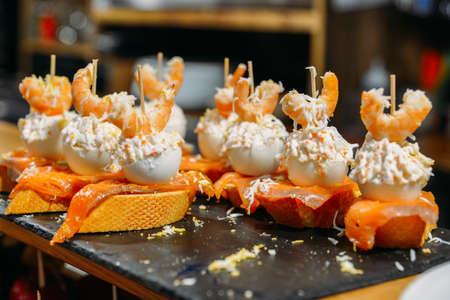 Tapas españolas llamados pintxos del País Vasco servido en una barra de bar en un restaurante en San Sebastián, España
