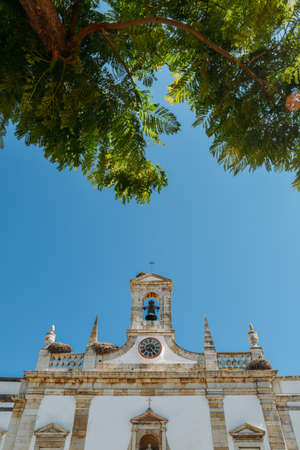 Faro, Portugal - July 16, 2018: Architecture details of the Arco de Vila, arch of the city, one of the gateways of the city built in the medieval era. Giant bird nests are visible Foto de archivo - 111316103
