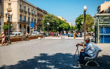 Older gentlemen relax in the shade at Rambla Nova in Tarragona, Catalonia, Spain