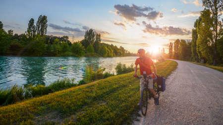 Man mountain biking on a gravel path along the Mincio River towards Mantova in Veneto, Italy at sunset