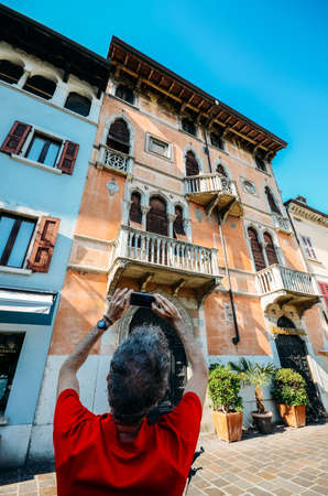 Wide angle view of man taking a picture of a traditional Venetian-style architeture close up on building facade