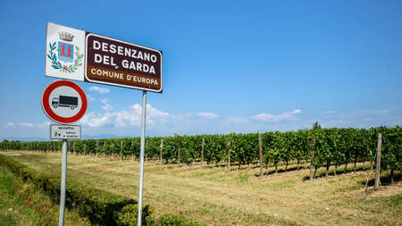 Sign welcoming visitors to Desenzano del Garda, Italy, with vineyards in the background Editorial