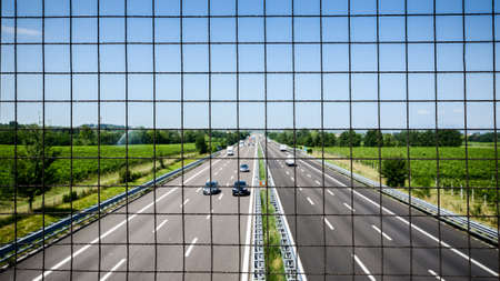 Image of chain link fence on bridge over pass. Chain fence on bridge above highway. Abstract industrial image of chain link fence and cars on highway. Stock Photo