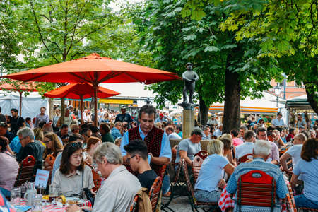 Locals and tourists enjoy beer and food at an open air beer garden in Viktualienmarkt in the historic centre of Munich, Germany