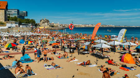 Crowded sandy beach in Cascais near Lisbon, Portugal during the summer. This beach is known as Praia da Conceicao