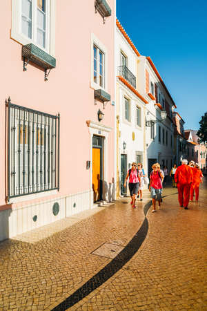 Tourists walking on Cascais street scene with typical Portuguese architecture and cobblestones in the historic centre