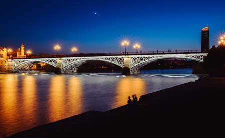 Long exposure blue hour view of Puente de Triana or Triana Bridge in Seville, Andalusia, Spain