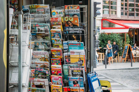 Close up of newspapers and magazines on a rack at a kiosk in central Paris