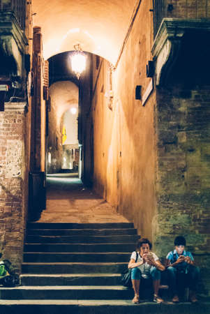 two tourists with their cell phones at a dark alleyway in the historic centre of Siena, Italy