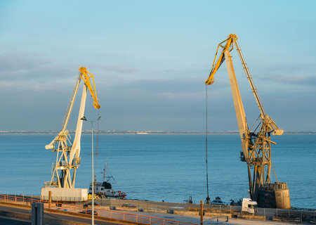 Gantry cranes load containers on a container ship in unidentifitable harbour. Stock Photo