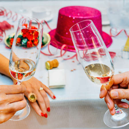 Clinking glasses of champagne in hands with party background - New Years' theme