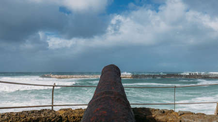 Antique black canon pointing towards ocean at Ericeira, Portugal