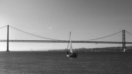 Sailboats with white sails on the Tagus River, 25 of April Bridge, Lisbon, Portugal - monochrome Archivio Fotografico