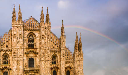 Facade of Milan, Italys Duomo cathedral with a beautiful rainbow on background