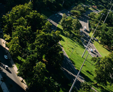 High angle aerial perspective of seemingly miniature cars on highway in between a park - deliberate dutch angle
