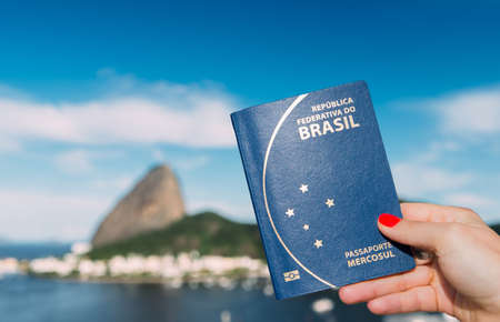 Hand holding Brazilian passport with SugarLoaf Mountain in Rio de Janeiro, Brazil in background Stock Photo