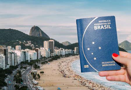 Woman holding a Brazilian passport overlooking Copacabana Beach, Rio de Janeiro, Brazil