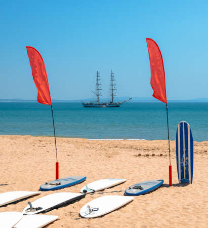 Standup Paddle boards on beach with bokeh caravel in background