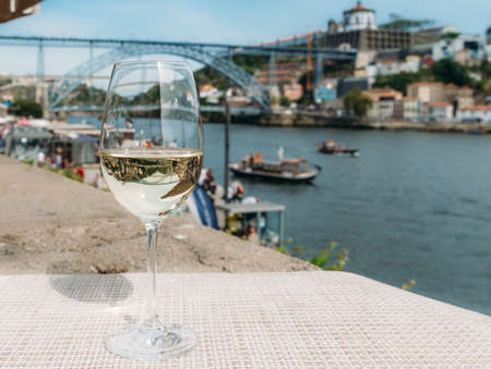 White wine glass overlooking Cais da Ribeira on the River Douro in Porto, Portugal Stock Photo