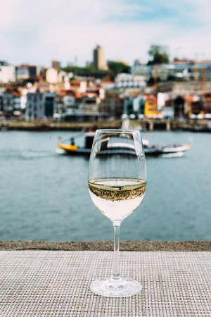 White wine glass overlooking Vila Nova de Gaia riverbank, Porto, Portugal