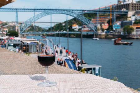 Red wine glass overlooking Cais da Ribeira on the River Douro in Porto, Portugal Stock Photo