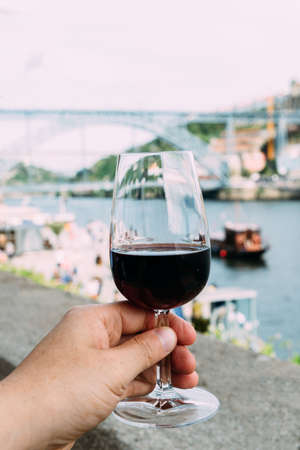 Hand holding glass of red wine in Porto, Portugal Imagens - 123225596