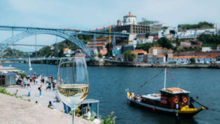 White wine glass overlooking Cais da Ribeira on the River Douro in Porto, Portugal Banque d'images