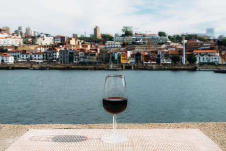 Glass of red Port wine overlooking Vila Nova de Gaia, Porto, Portugal