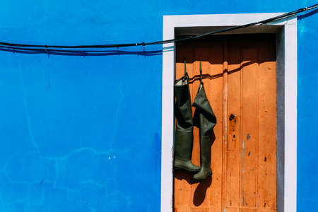 Pair of wellies hanging from brown rustic doorway with bright blue wall facade copy space Stockfoto