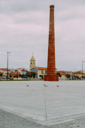 Old fashioned brick chimney in Espinho, Portugal next to an old church