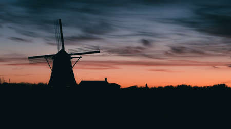 Silhouette of traditional Dutch windmill at sunset at sunset Banco de Imagens