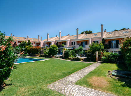 Generic wealthy residential complex of modern condos with shared swimming pool in Portugal