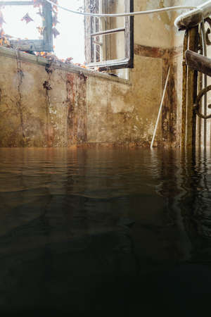 Flooded derelict staircase with sunlight coming through window